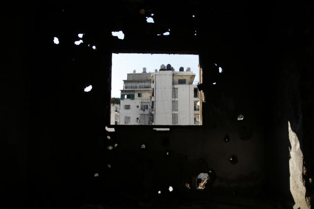 In this Nov. 17, 2018, photo, Shiyah, a Muslim Shiite neighborhood is seen from a destroyed apartment in the southern Beirut Christian district of Ain el-Rummaneh, Lebanon. The two sides fought fierce battles during the 1975-90 civil war, which started with a shooting on a bus in Ain el-Rummaneh. (AP Photo/Hassan Ammar)