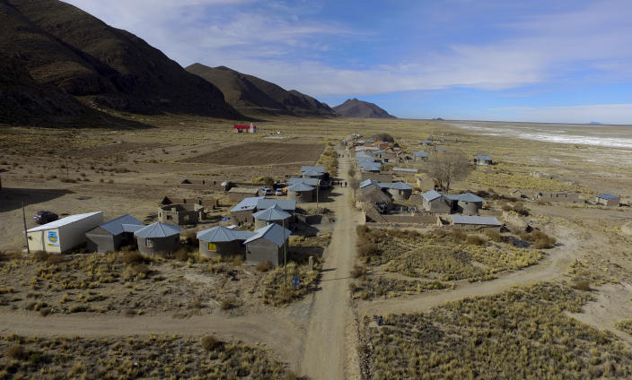 Residents walk along a dirt road in the Urus del Lago Poopo indigenous community, which sits along the salt-crusted former shoreline of Lake Poopo, in Punaca, Bolivia, Monday, May 24, 2021. Bolivia's second-largest lake dried up about five years ago, victim of shrinking glaciers, water diversions for farming and contamination. (AP Photo/Juan Karita)