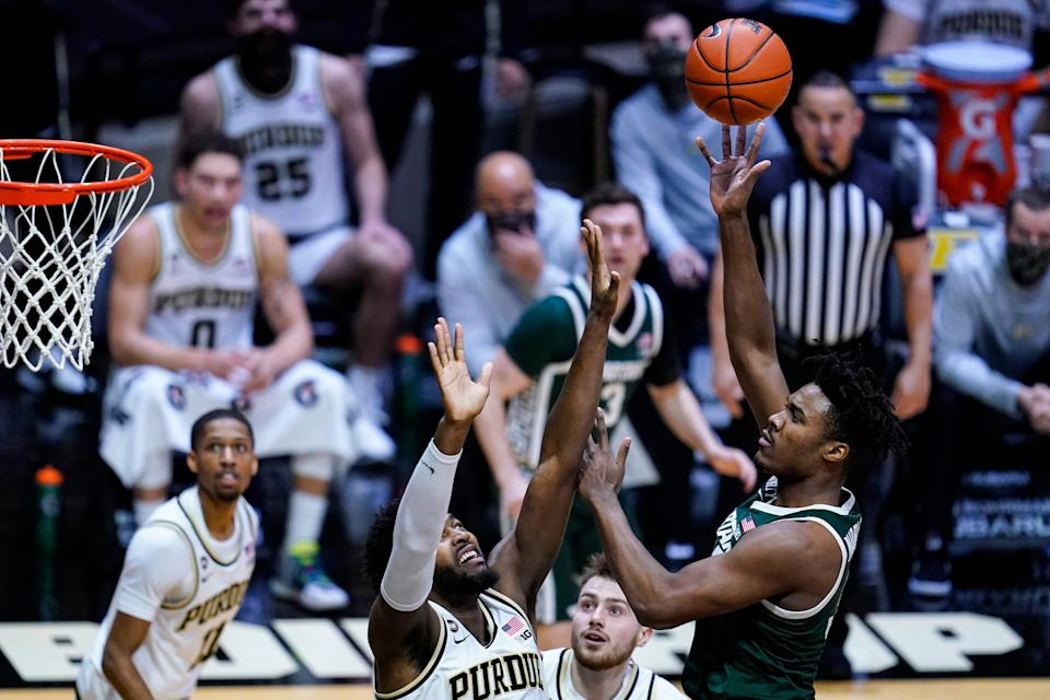 Michigan State forward Julius Marble II (34) shoots over Purdue forward Trevion Williams during the first half of an NCAA college basketball game in West Lafayette, Ind., Tuesday, Feb. 16, 2021. (AP Photo/Michael Conroy)