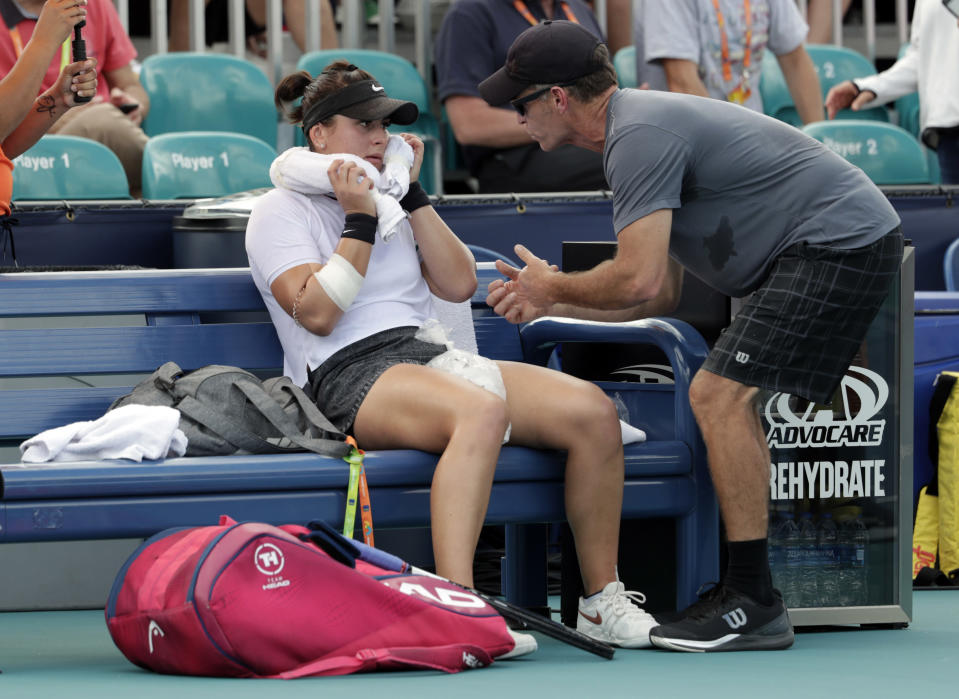 """FILE - In this March 21, 2019 file photo, Bianca Andreescu, of Canada, left, talks with her coach Sylvain Bruneau during her match against Irina Camelia Begu, of Romania, at the Miami Open tennis tournament in Miami Gardens, Fla. Bruneau has released a statement, Sunday, Jan. 17, 2021, saying he was the positive coronavirus case aboard the flight from Abu Dhabi to Melbourne and he had followed all protocols and procedures, including producing a negative test within 72 hours before the flight departure and has """"no idea how I might have contracted the virus."""" (AP Photo/Lynne Sladky, File)"""