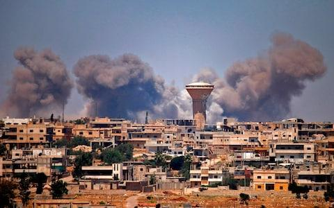 <span>Smoke rises above rebel-held areas of the city of Deraa during reported airstrikes by Syrian regime forces on July 5, 2018.</span> <span>Credit: AFP </span>