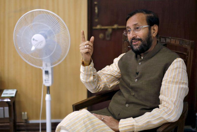 India's Environment Minister Javadekar speaks on his phone before an interview with Reuters inside his office in New Delhi