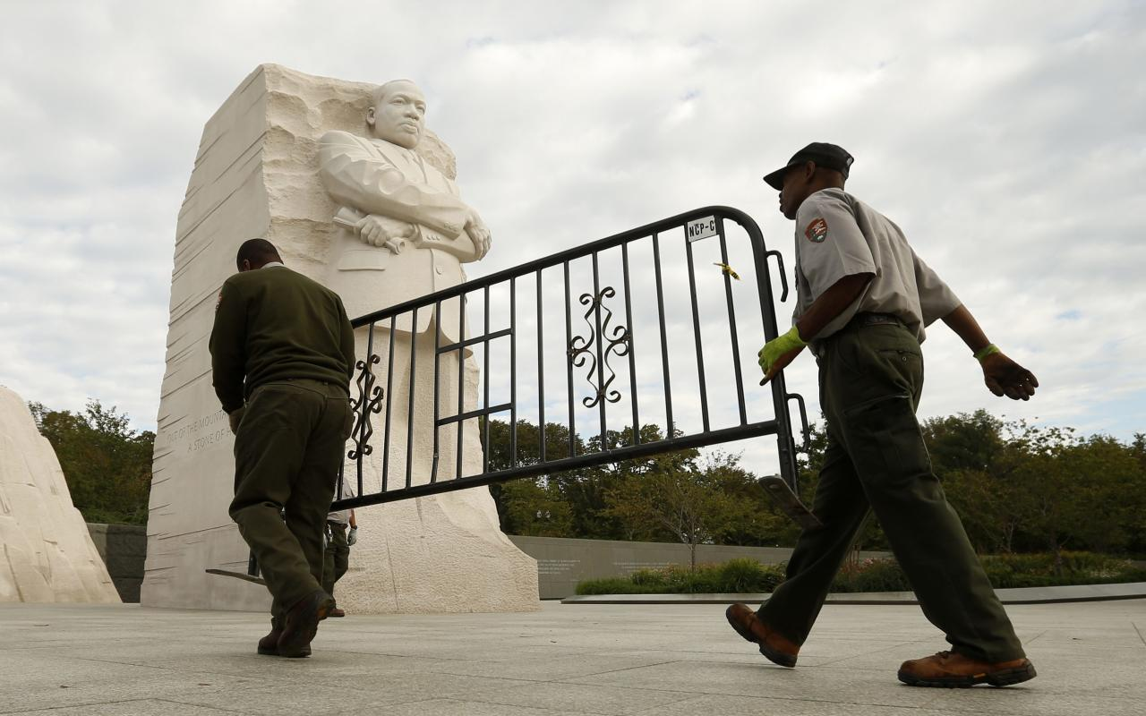 REFILE - CORRECTING TYPO National Park workers remove a barricade at the Martin Luther King Jr. Memorial as it reopens to the public in Washington October 17, 2013. The White House moved quickly early on Thursday to get the U.S. government back up and running after a 16-day shutdown, directing hundreds of thousands of workers to return to work. REUTERS/Kevin Lamarque (UNITED STATES - Tags: POLITICS BUSINESS)