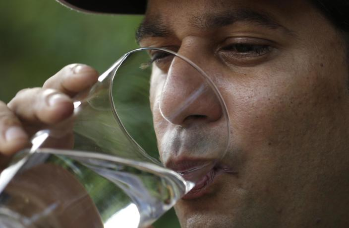 Alain Izquierdo, a Havana butcher and one of 15 survivors of the 32 Cuban migrants who were left adrift in Caribbean waters during their voyage, takes a drink of water while speaking with Reuters at his uncle's home in Port St. Lucie, Florida, October 3, 2014. The group of Cuban migrants drank their own urine and blood after the engine of their homemade boat failed, leaving them adrift in the Caribbean for three weeks without food or water, according to survivors who reached the United States this week. Picture taken October 3, 2014. REUTERS/Rickey Rogers (UNITED STATES - Tags: POLITICS SOCIETY IMMIGRATION DISASTER)