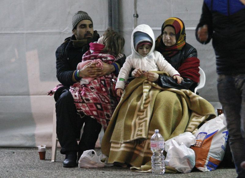 Migrants rest after disembarking from the Sierra Leone-flagged vessel Ezadeen at Corigliano Calabro harbor, southern Italy January 3, 2015. The cargo ship had been drifting powerless after running out of fuel about 40 miles from Italy's southern coast with as many as 450 people onboard.    REUTERS/Antonino Condorelli (ITALY - Tags: SOCIETY IMMIGRATION CRIME LAW POLITICS MARITIME TPX IMAGES OF THE DAY)