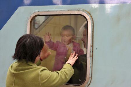 A Chinese baby waves to his mother as he and his father depart from Shanghai's train station, December 29, 2005. REUTERS/Nir Elias