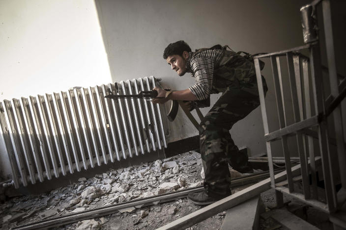 In this Tuesday, Oct. 30, 2012 photo, a rebel fighter belonging to the Liwa Al-Fatah takes cover as he aims at an enemy position from a school building during skirmishes with the Syrian army in the nearby Bustan Al-Pasha front line in Aleppo, Syria.(AP Photo/Narciso Contreras)