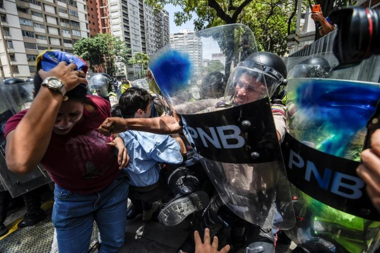 An estimated 1,000 people scuffled with police as they tried to march to Venezuela's National Assembly to demand the government restore powers to its opposition majority