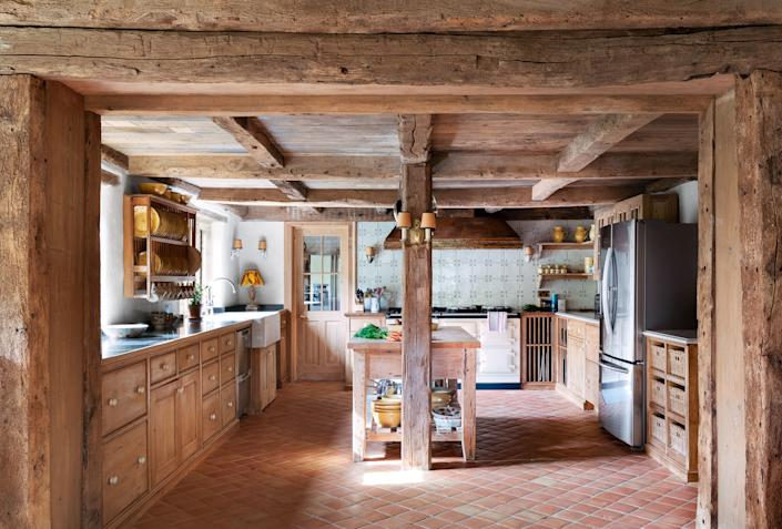 """<div class=""""caption""""> The custom kitchen is by <a href=""""http://www.coryndon.co.uk/"""" rel=""""nofollow noopener"""" target=""""_blank"""" data-ylk=""""slk:Coryndon"""" class=""""link rapid-noclick-resp"""">Coryndon</a>. Sink from <a href=""""http://ronsonreclaim.com/"""" rel=""""nofollow noopener"""" target=""""_blank"""" data-ylk=""""slk:Ronson Reclaim"""" class=""""link rapid-noclick-resp"""">Ronson Reclaim</a> with <a href=""""https://www.waterworks.com/us_en/"""" rel=""""nofollow noopener"""" target=""""_blank"""" data-ylk=""""slk:Waterworks"""" class=""""link rapid-noclick-resp"""">Waterworks</a> fittings; range by <a href=""""https://www.aga-ranges.com/"""" rel=""""nofollow noopener"""" target=""""_blank"""" data-ylk=""""slk:AGA"""" class=""""link rapid-noclick-resp"""">AGA</a>; refrigerator by <a href=""""https://www.samsung.com/us/"""" rel=""""nofollow noopener"""" target=""""_blank"""" data-ylk=""""slk:Samsung"""" class=""""link rapid-noclick-resp"""">Samsung</a>; copper countertop and hood by artist Diarmuid Byron-O'Connor. </div>"""