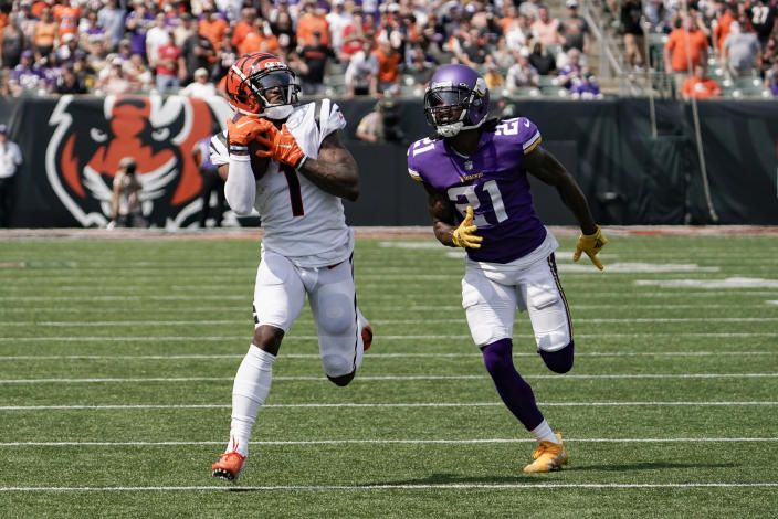 Cincinnati Bengals wide receiver Ja'Marr Chase (1) makes a catch and takes it in for a touchdown past Minnesota Vikings defensive back Bashaud Breeland (21) in the first half of an NFL football game, Sunday, Sept. 12, 2021, in Cincinnati. (AP Photo/Jeff Dean)