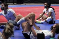 Outside hitter Aury Cruz, top right, and teammates stretch following an afternoon volleyball practice in Dallas, Wednesday, Feb. 24, 2021. (AP Photo/Tony Gutierrez)