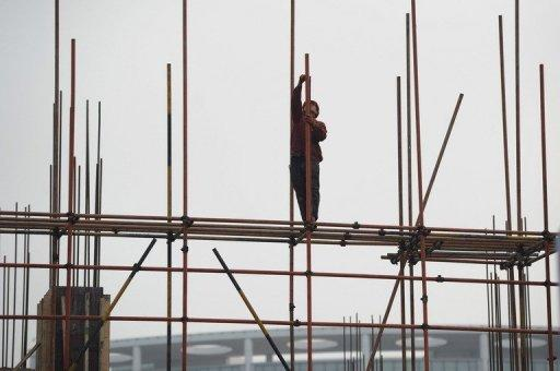 Construction labourers are seen working at a highrise building construction site in Hefei, east China's Anhui province. China's inflation rate eased to 3.0 percent in May, its lowest level since June 2010, according to latest official data, giving the government further room to loosen credit to boost flagging growth