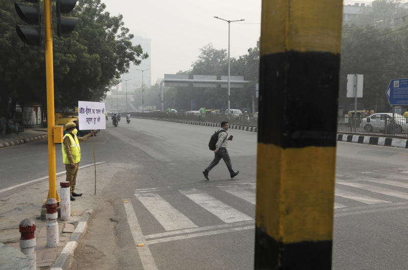 A policewoman wears a pollution mask and and hold a banner saying obey odd and even, remove pollution, in New Delhi, India, Nov. 4, 2019. (Photo: Manish Swarup/AP)