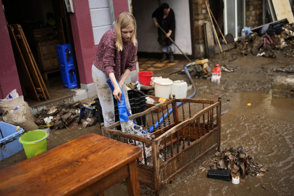 A woman washes mud and debris out of a baby crib outside of her house after flooding in Ensival, Verviers, Belgium, Friday July 16, 2021. Severe flooding in Germany and Belgium has turned streams and streets into raging torrents that have swept away cars and caused houses to collapse. (AP Photo/Francisco Seco)