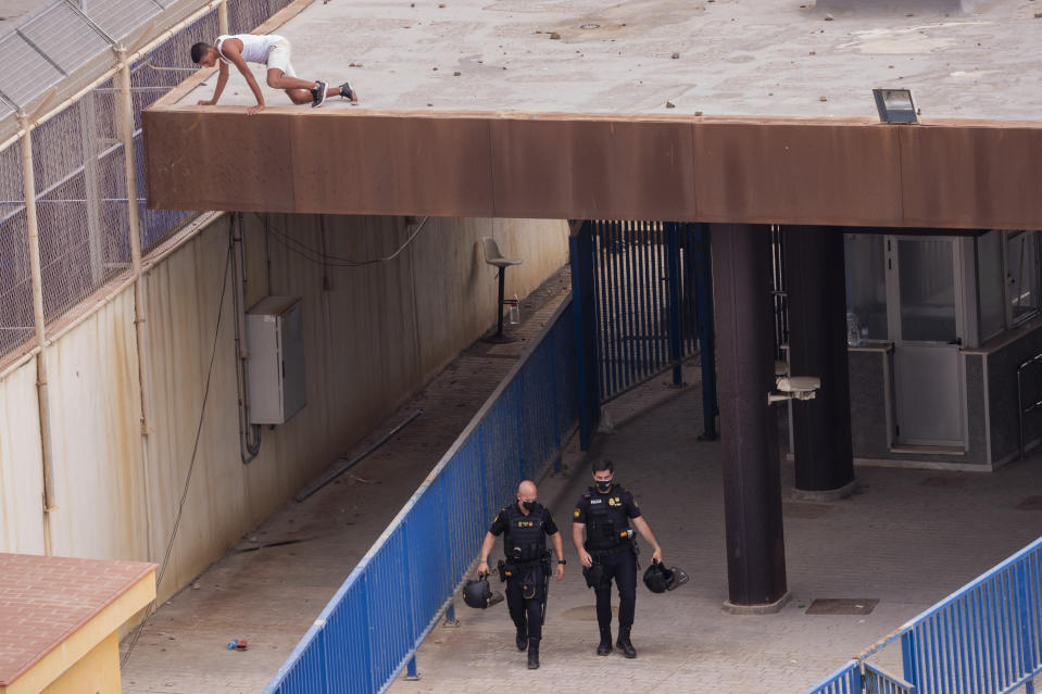 An unaccompanied minor who crossed into Spain hides atop of a rooftop in the Spanish enclave of Ceuta, next the border between Spain and Morocco, Wednesday, May 19, 2021. (AP Photo/Bernat Armangue)