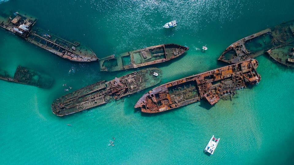 <p>Small speed boats explore the turquoise waters that house a ship graveyard full of yesteryear's vessels. </p>