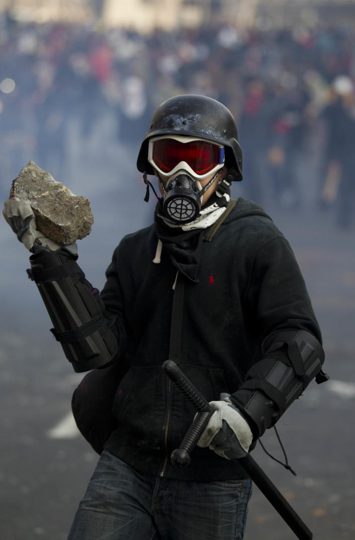 A protestor holds a rock during clashes with police outside the steel security barriers around the National Congress, where the swearing in of new Mexican President Enrique Pena Nieto is taking place in Mexico City, Saturday Dec. 1, 2012. Pena Nieto took power at midnight in a symbolic ceremony and will formally take the oath of office Saturday morning after campaigning as the face of a new PRI, a party that claims to be repentant and reconstructed after voted out of the presidency in 2000. (AP Photo/Eduardo Verdugo)