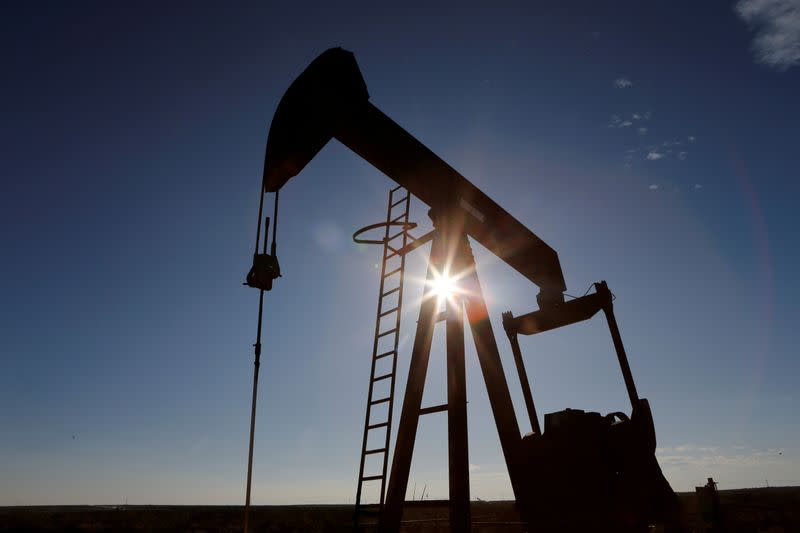 FILE PHOTO: The sun is seen behind a crude oil pump jack in the Permian Basin in Loving County