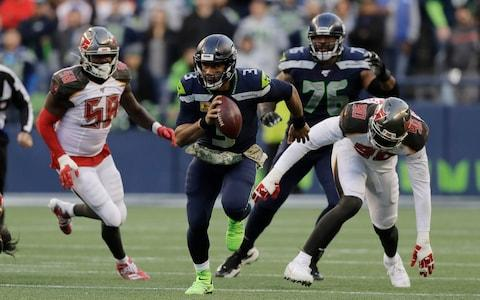 Seattle Seahawks quarterback Russell Wilson (3) scrambles away from Tampa Bay Buccaneers defensive end Jason Pierre-Paul (90) during overtime of an NFL football game, Sunday, Nov. 3, 2019, in Seattle - Credit: AP