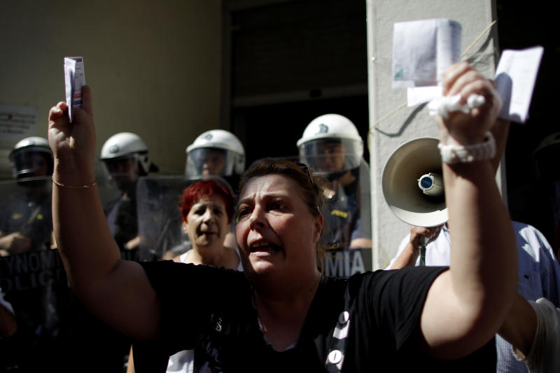 FILE- In this Sept. 28, 2012 file photo, private hospital nurse Paraskevi Petropoulou holds up her unpaid electricity and income tax bills during a protest outside the Health Ministry in central Athens. Petropoulou said that she has not been paid for more than five months, because the government owes money to private hospitals who in turn are unable to pay their employees. To the casual visitor, all might appear well in Athens, but scratch the surface and you find a society in freefall, ripped apart by the most vicious financial crisis the country has seen in half a century. (AP Photo/Petros Giannakouris, File)