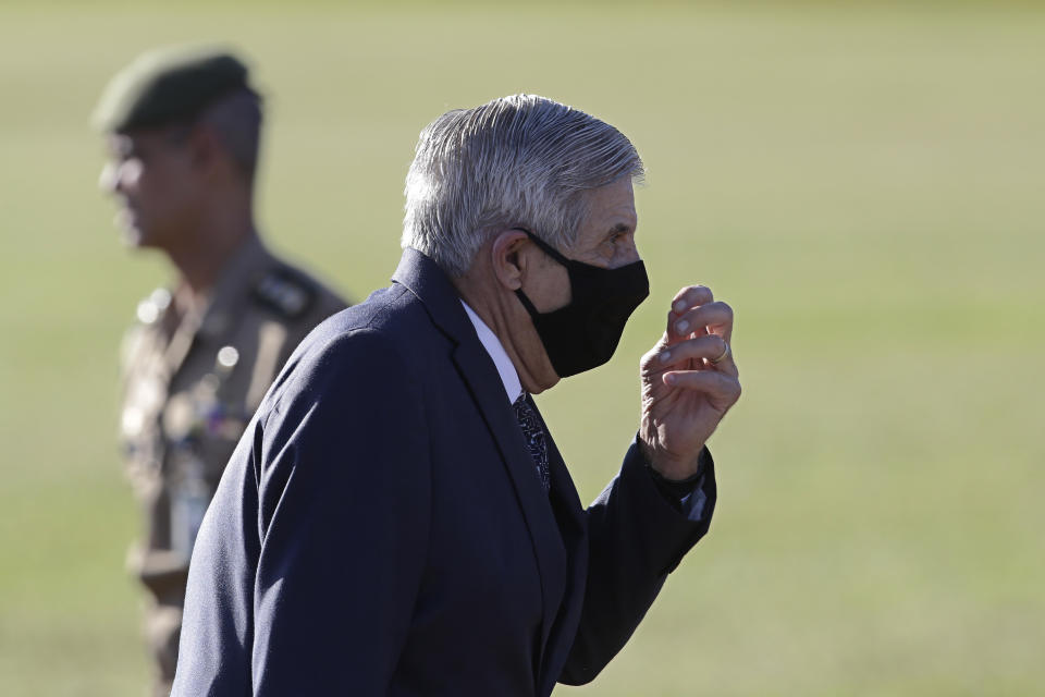 Gen. Augusto Heleno, Brazil's Minister of the Internal Security, walks away after a flag raising ceremony outside Alvorada palace, the presidential residence in Brasilia, Brazil, Tuesday, May 12, 2020. The morning ceremony flew Brazil's flag at half mast to mourn those who have died from the new coronavirus. (AP Photo/Eraldo Peres)