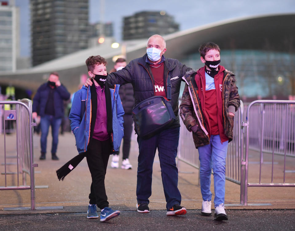 Fans wearing a protective face mask walk towards the stadium before the English Premier League soccer match between West Ham United and Manchester United at the London stadium in London, England, Saturday, Dec. 5, 2020. (Justin Setterfield/Pool Via AP)