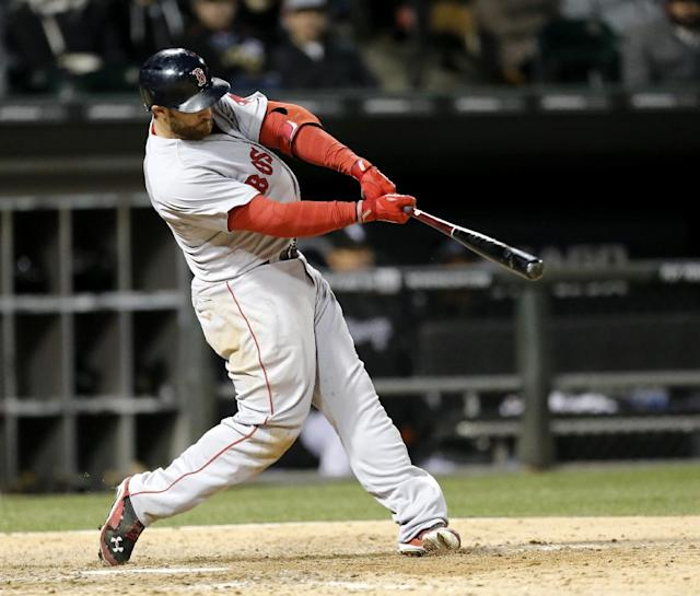Boston Red Sox's Jonny Gomes hits a sacrifice fly off a pitch by Chicago White Sox relief pitcher Daniel Webb, scoring Dustin Pedroia, during the 11th inning of a baseball game Wednesday, April 16, 2014, in Chicago. (AP Photo/Charles Rex Arbogast)