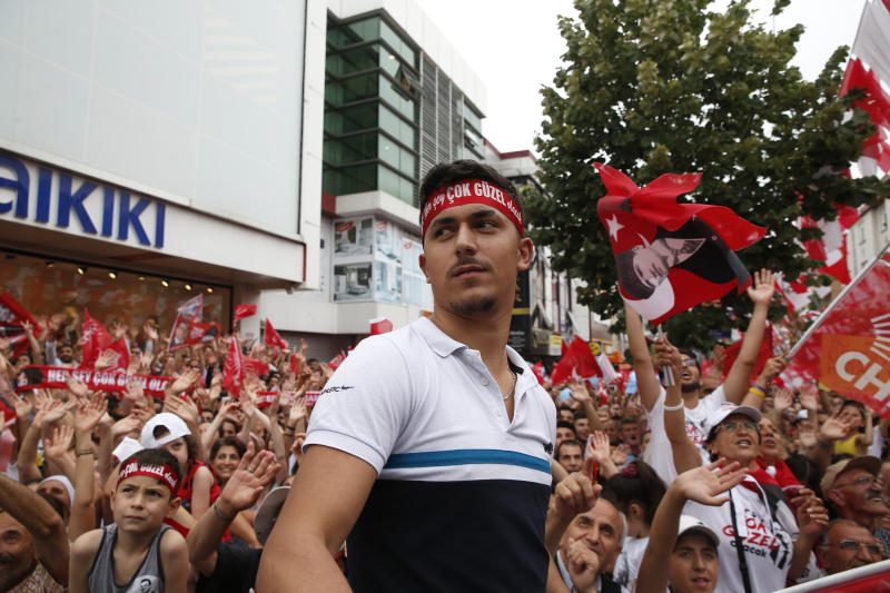 In this Wednesday, June 19, 2019 photo, supporters of Ekrem Imamoglu, candidate of the secular opposition Republican People's Party, or CHP watch him delivering a speech during a rally in Istanbul, ahead of the June 23 re-run of Istanbul elections. Voters in Istanbul return to the polls on Sunday for a rerun of the election for the mayor of the city. (AP Photo/Lefteris Pitarakis)