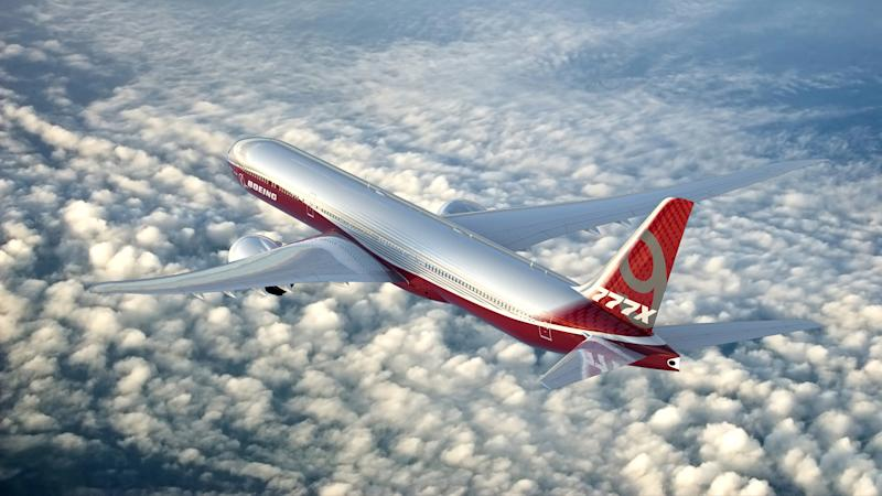 A rendering of a 777-9 flying above clouds.