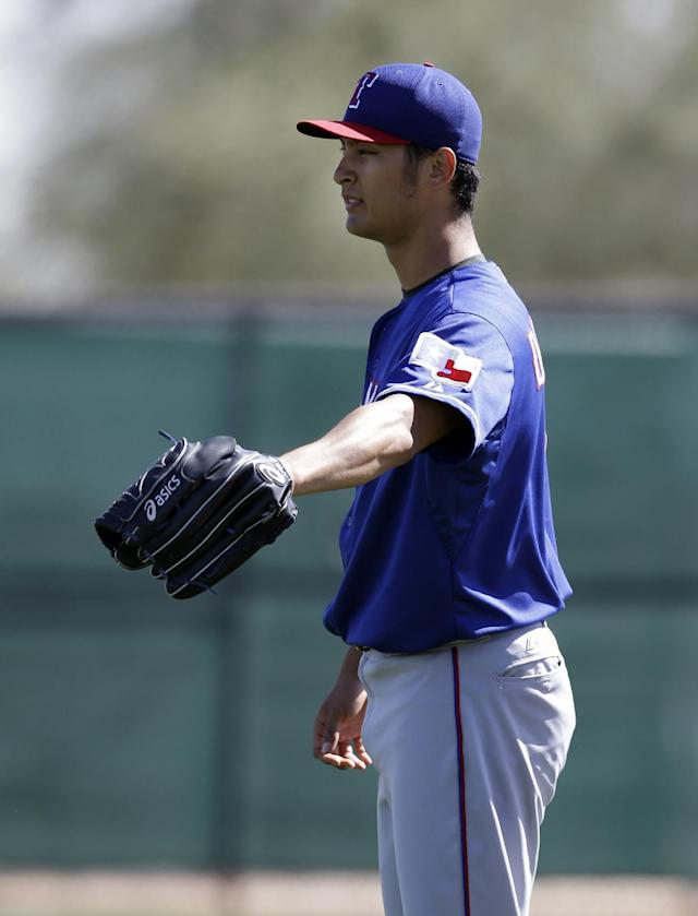 Texas Rangers' Yu Darvish of Japan motions to teammates before throwing in an intrasquad game during spring training baseball practice, Monday Feb. 24, 2014, in Surprise, Ariz. (AP Photo/Tony Gutierrez)