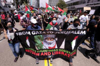 Demonstrators holding signs and the flag of Palestine march to the Israeli Consulate during a protest against Israel and in support of Palestinians during the current conflict in the Middle East, Saturday, May 15, 2021, in the Westwood section of Los Angeles. (AP Photo/Ringo H.W. Chiu)