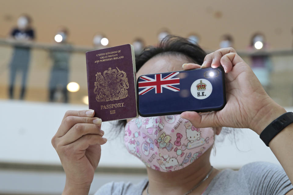 A protester holds a British National (Overseas) passport in a shopping mall during a protest against China's national security legislation for the city, in Hong Kong, Friday, May 29, 2020. The British government says t it will grant hundreds of thousands of Hong Kong residents greater visa rights if China doesn't scrap a planned new security law for the semi-autonomous territory. U.K. Foreign Secretary Dominic Raab said about 300,000 people in Hong Kong who hold British National (Overseas) passports will be able to stay in Britain for 12 months rather than the current six. (AP Photo/Kin Cheung)