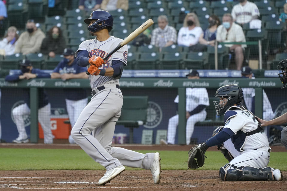 Houston Astros' Taylor Jones watches his RBI single next to Seattle Mariners catcher Luis Torrens during the fourth inning of a baseball game Saturday, April 17, 2021, in Seattle. Michael Brantley scored. (AP Photo/Ted S. Warren)