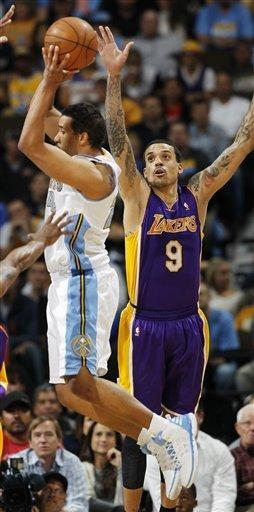 Denver Nuggets guard Andre Miller, left, pulls in a loose ball as Los Angeles Lakers forward Matt Barnes covers in the first quarter of Game 4 of the teams' first-round NBA basketball series in Denver on Saturday, May 5, 2012. (AP Photo/David Zalubowski)