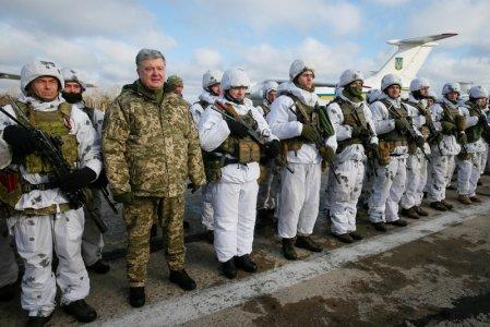 FILE PHOTO: Ukraine's President Petro Poroshenko (2nd L, front) poses for a picture with servicemen as he visits an airforce base near Zhytomyr, Ukraine December 6, 2018. REUTERS/Gleb Garanich