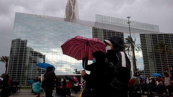 PHOTO: People wear masks and carry umbrellas in the rain, while social distancing due to COVID-19, during a Christmas Eve Roman Catholic Mass at Christ Cathedral on Dec. 24, 2020 in Garden Grove, Calif. (Patrick T. Fallon/AFP via Getty Images)