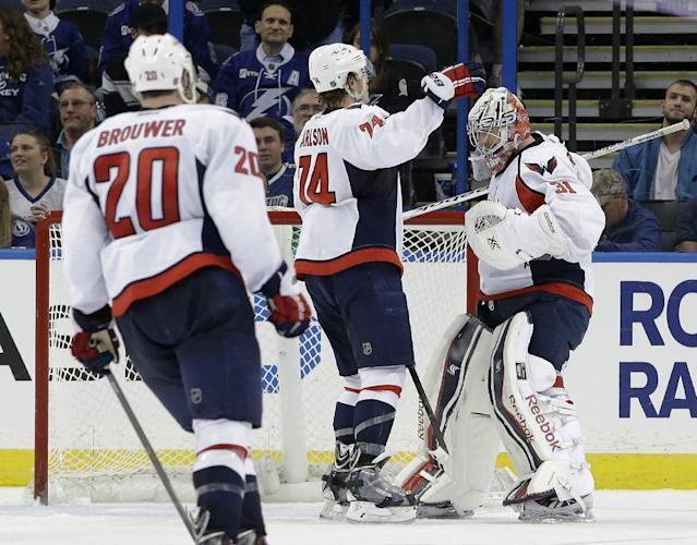 Washington Capitals goalie Philipp Grubauer (31), of Germany, celebrates with teammates defenseman John Carlson (74) and right wing Troy Brouwer (20) after the Capitals defeated the Tampa Bay Lightning 4-3 during an NHL hockey game Thursday, Jan. 9, 2014, in Tampa, Fla. (AP Photo/Chris O'Meara)