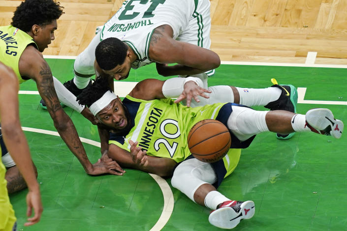 Boston Celtics center Tristan Thompson (13) comes in to tie up the ball with Minnesota Timberwolves forward Josh Okogie (20) during the second quarter of an NBA basketball game Friday, April 9, 2021, in Boston. (AP Photo/Elise Amendola)
