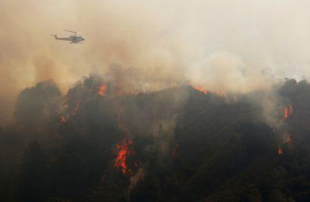 A Cal Fire helicopter flies over Williams Canyon during the Soberanes Fire near Carmel Valley, California, U.S. July 29, 2016. REUTERS/Michael Fiala