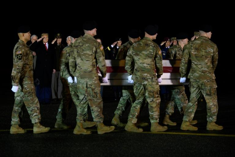 US President Donald Trump salutes as he observes the dignified transfer of two US soldiers, killed in Afghanistan, at Dover Air Force Base in Delaware in February 2020 (AFP Photo/JIM WATSON)