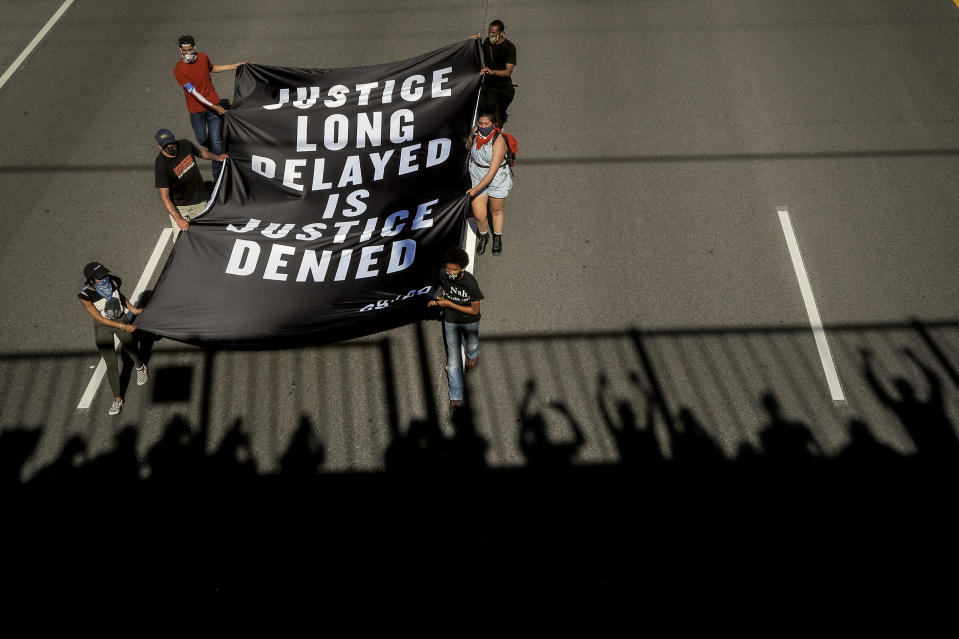 FILE - This photo from Sunday May 31, 2020, shows protesters displaying a banner along a Minneapolis highway calling for justice in the death of George Floyd. The chaos unleashed in 2020, amid the coronavirus pandemic, has created space for different voices to speak, for different conversations to be had and for different questions to be asked. (AP Photo/Julio Cortez, File)