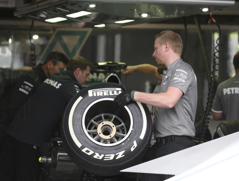 FILE- In this Thursday, June 6, 2013 file photo, a Mercedes mechanic holds a tire in the pit, at the Gilles Villeneuve racetrack, in Montreal, Canada. A tire testing session involving Mercedes and Pirelli that was criticized by rival Formula One teams will be referred to the FIA's international tribunal as a possible breach of the sport's rules. (AP Photo/Luca Bruno, file)