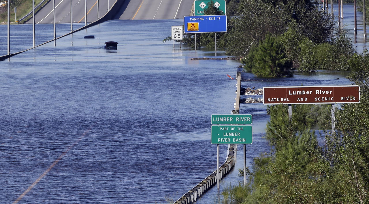 The Lumber River overflows onto a stretch Interstate 95 in Lumberton, N.C., Tuesday, Sept. 18, 2018, following flooding from Hurricane Florence. (AP Photo/Gerry Broome)