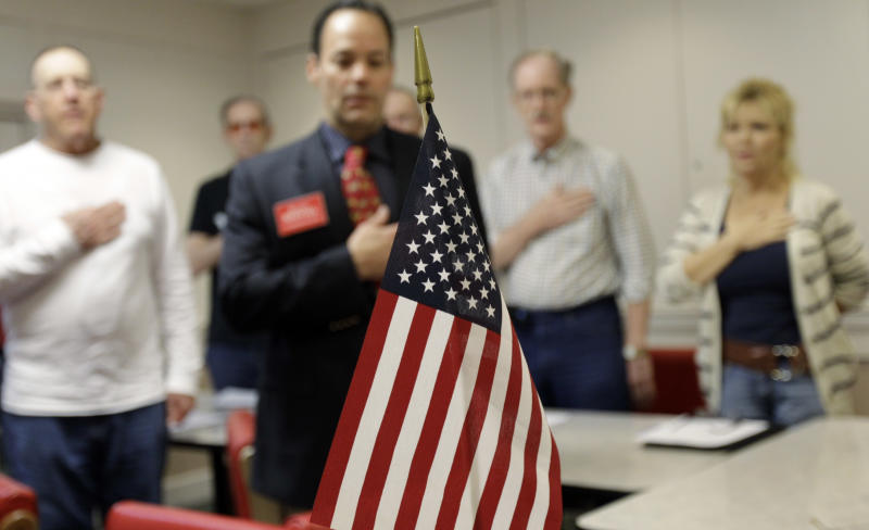 In this Tuesday, March 20, 2012 photo, attendees hold their hands over their hearts as they say the Pledge of Allegiance during a tea party meeting in a restaurant in San Antonio with a U.S. flag in the foreground. Following the tide-turning elections of 2010, when the tea party revolution sent new conservatives to governors' mansions, statehouses and, of course, Congress, what's the group's role now? The tea party has changed, but it's very much alive. (AP Photo/Eric Gay)