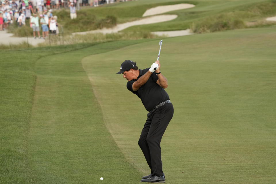 Phil Mickelson hits his second shot on the 18th hole during the third round at the PGA Championship golf tournament on the Ocean Course, Saturday, May 22, 2021, in Kiawah Island, S.C. (AP Photo/David J. Phillip)