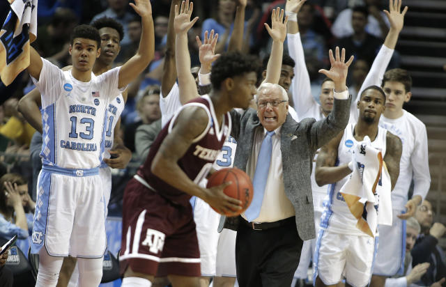 North Carolina head coach Roy Williams, center, and players on the bench raise their arms as Texas A&M's Jay Jay Chandler (0) looks to shoot during the second half of a second-round game in the NCAA men's college basketball tournament in Charlotte, N.C., Sunday, March 18, 2018. (AP Photo/Bob Leverone)