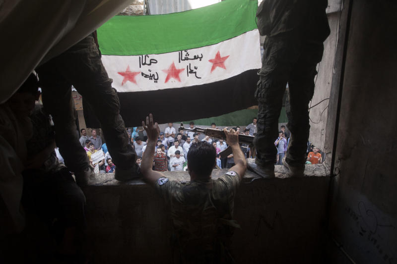 """In this Friday, Sept. 21, 2012 photo, Free Syrian Army rebels hold a revolutionary flag on it during a demonstration in the Bustan al-Qasr neighborhood of Aleppo, Syria. The Britain-based Syrian Observatory for Human Rights said Friday that nearly 30,000 Syrians have been killed during the 18-month uprising against the Assad regime. Arabic on flag is reversed, but reads, """"God welcome, free people."""" (AP Photo/ Manu Brabo)"""