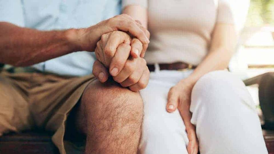 Close up shot of senior couple holding hand. Loving couple sitting together and holding hands. Focus on hands.