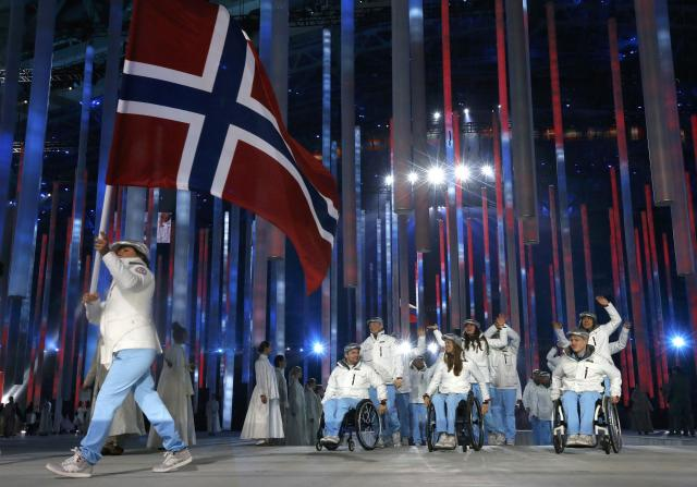 Norway's flag-bearer Mariann Marthinsen (L), leads his country's contingent during the opening ceremony of the 2014 Paralympic Winter Games in Sochi, March 7, 2014. REUTERS/Alexander Demianchuk (RUSSIA - Tags: OLYMPICS SPORT)