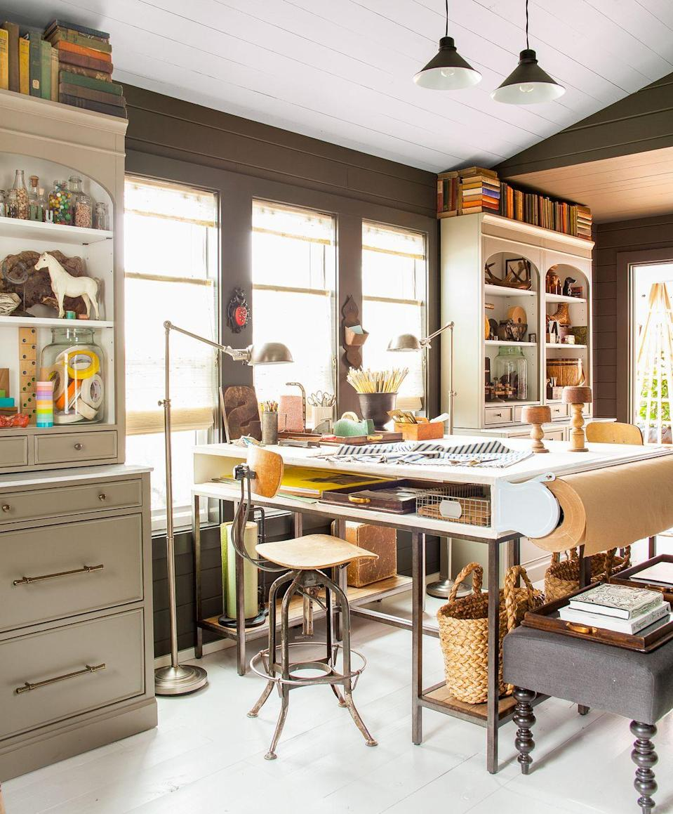 """<p>A horizontal paper cutter at the end of a counter-height desk allows for easy access to kraft paper for sketching, or gift wrap for presents. Designer <a href=""""http://www.barbarakurgan.com/"""" rel=""""nofollow noopener"""" target=""""_blank"""" data-ylk=""""slk:Barbara Kurgan"""" class=""""link rapid-noclick-resp"""">Barbara Kurgan</a> included a custom spot beneath the tabletop to keep often-used materials hidden but on hand. </p>"""
